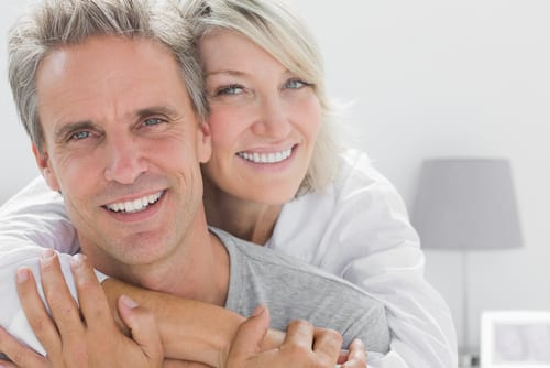 Affectionate couple smiling at camera at home in bedroom-img-blog