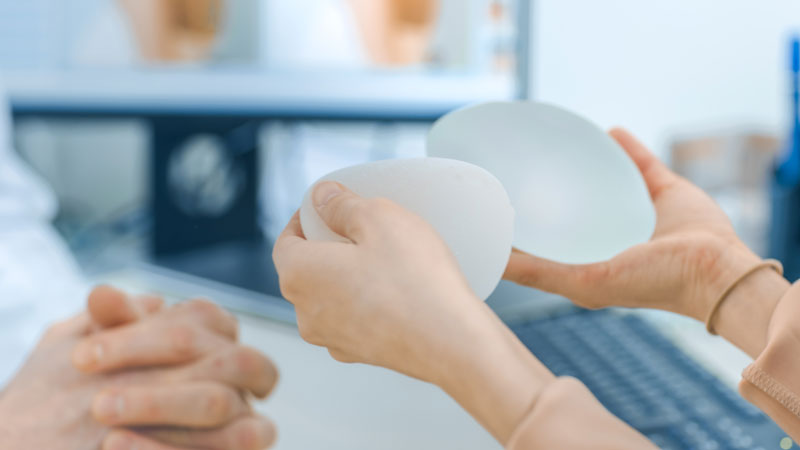Woman holding two breast implants at her doctor's office.