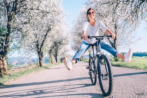 Happy woman riding a bike in spring.