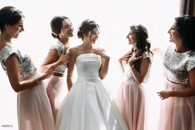 a bride chatting with her bridesmaids in a sleeveless dress.