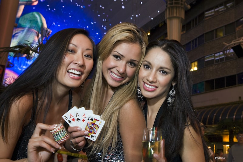 Three young women in a casino, holding up a deck of cards.