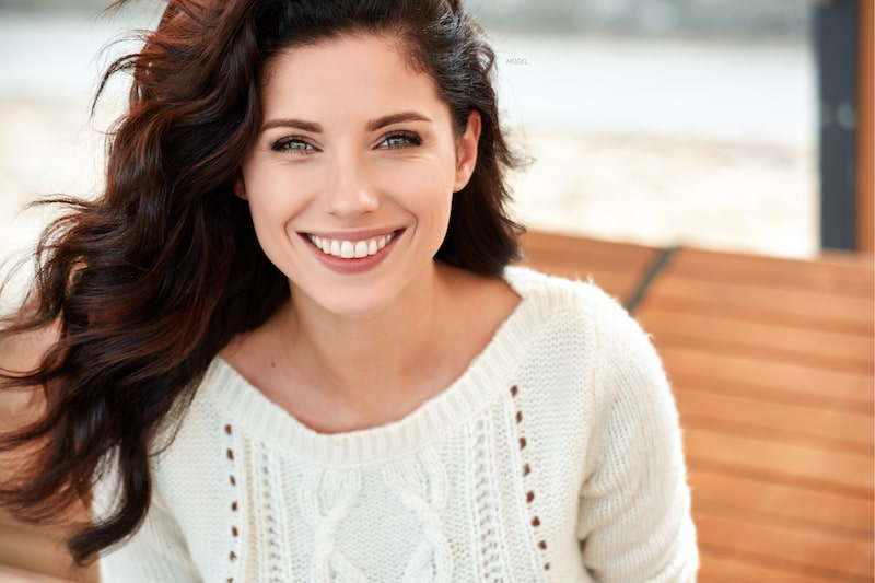 Smiling woman wearing a white knit sweater